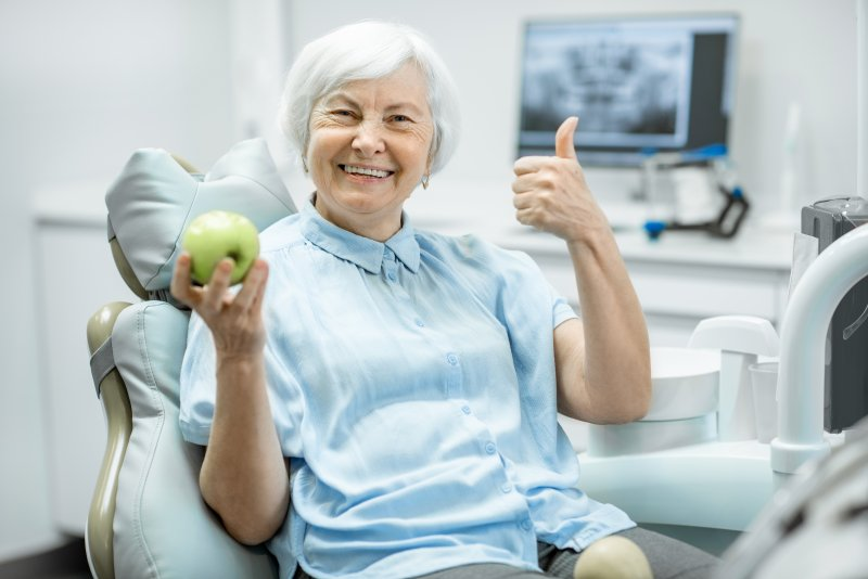 Woman smiling and holding a green apple